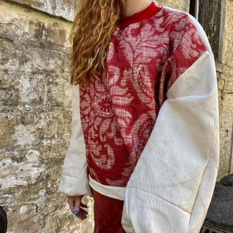 Red and white batwing jumper made from upcycled furnishing materials. Zero waste designer.