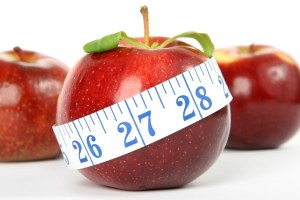 A red apple with a tape measure around it. Refers to a diet plan
