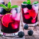 Blackberry Mojito drink in a short glass with blackberries, lime juice,mint leaves, simple syrup, and club soda. Garnished with lime slices, blackberries, and a sprig of mint.
