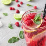 Raspberry mojito drink with raspberries, mint, sugar, club soda and rum. Served in a tall class with a sprig of mint and two raspberries as garnish.
