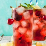 A tall glass with cherry, mint, lime, rum , simple syrup, and ice. Garnished with fresh cherries and a sprig of mint.