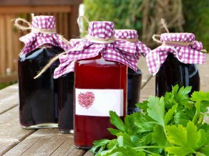 Four bottles of flavored syrups with cloth tied around the lids for decoration. One syrup color is red and the rest are purple. They are sitting on a wood table with greenery beside them.