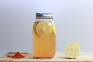 Lemon simple syrup in a mason jar with sliced lemon inside of jar and a half of lemon beside it.
