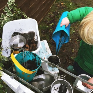 toddler playing with mud kitchen