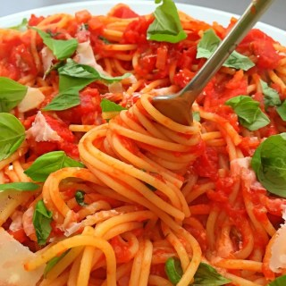plate full of spaghetti marinara with fork swirling into the spaghetti strands