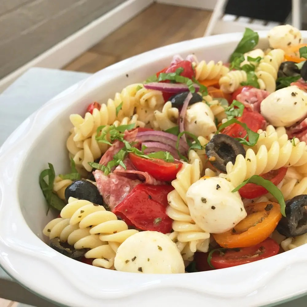 white bowl filled with Italian pasta salad loaded with mini mozzarella balls, red onions, salami, chargrilled peppers, baby tomatoes, olives and fresh herbs