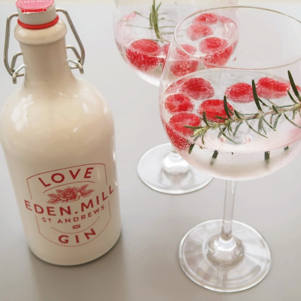 Eden Mills gin bottle with two glasses of gin and tonic garnished with raspberries and fresh rosemary