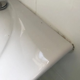 dirty bathroom sink with limescale on the tile sealant