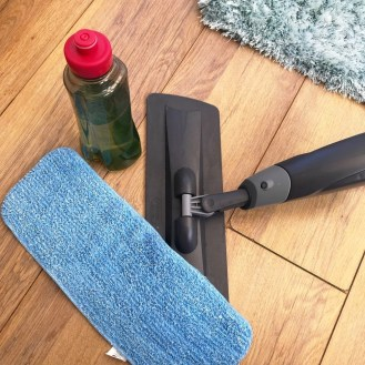 Addis spray mop head alongside the removable water bottle which is filled with water and lemon flash cleaner. Addis spray mop removable fleece head on floor by mop head