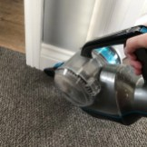 VAX Blade 32V cordless vacuum cleaner with the crevice tool being used to clean edges of carpet by the skirting board
