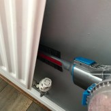 VAX Blade 32V cordless vacuum cleaner with the radiator tool to vacuum behind the radiator