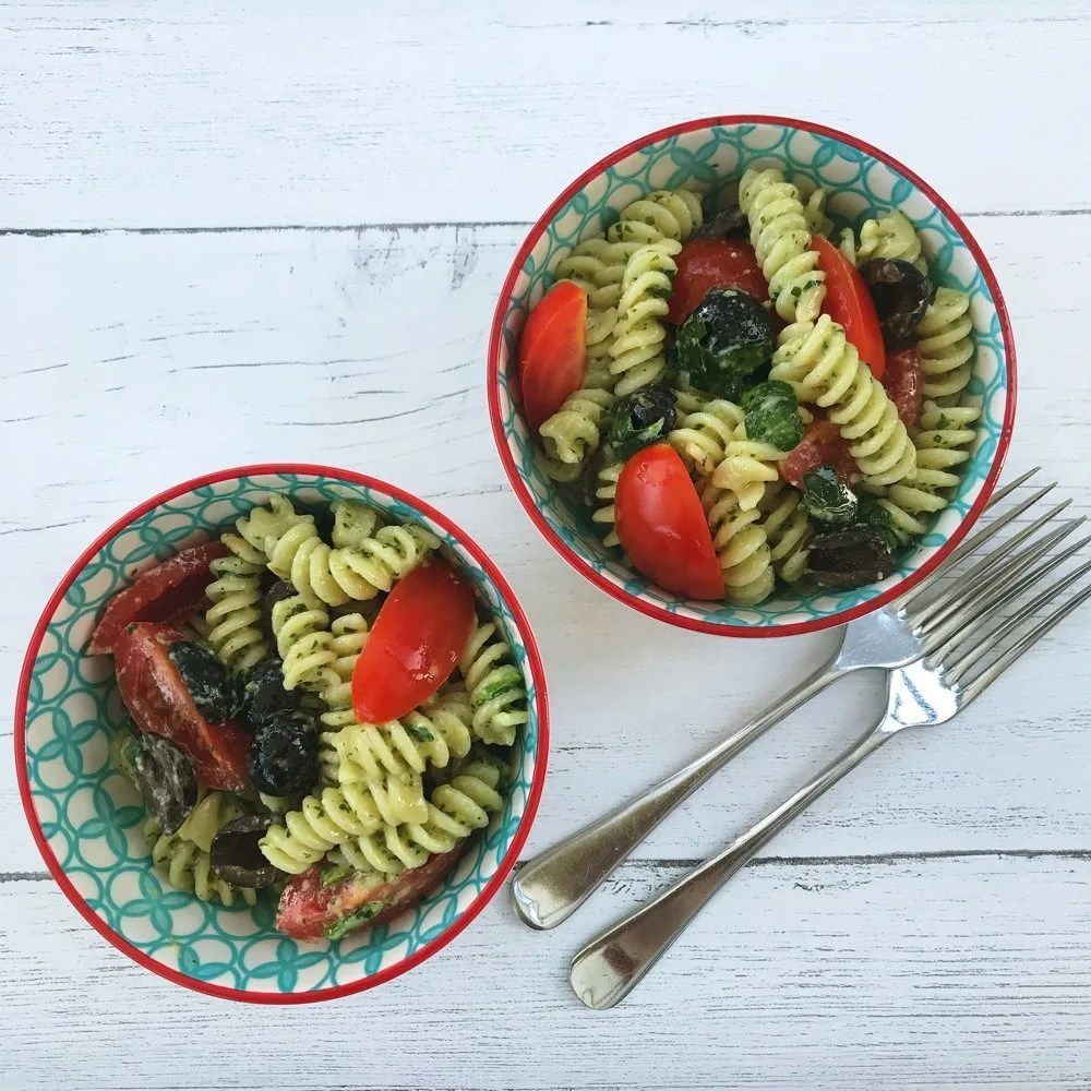 white wooden table with two bowls of pasta pesto using fusilli pasta, homemade pesto, spinach, black olives and baby plum tomatoes - two vintage silver forks by the bowls.
