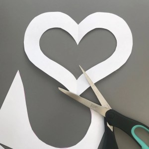 white paper heart stencil cut from A4 white paper - black and turquoise craft scissors alongside