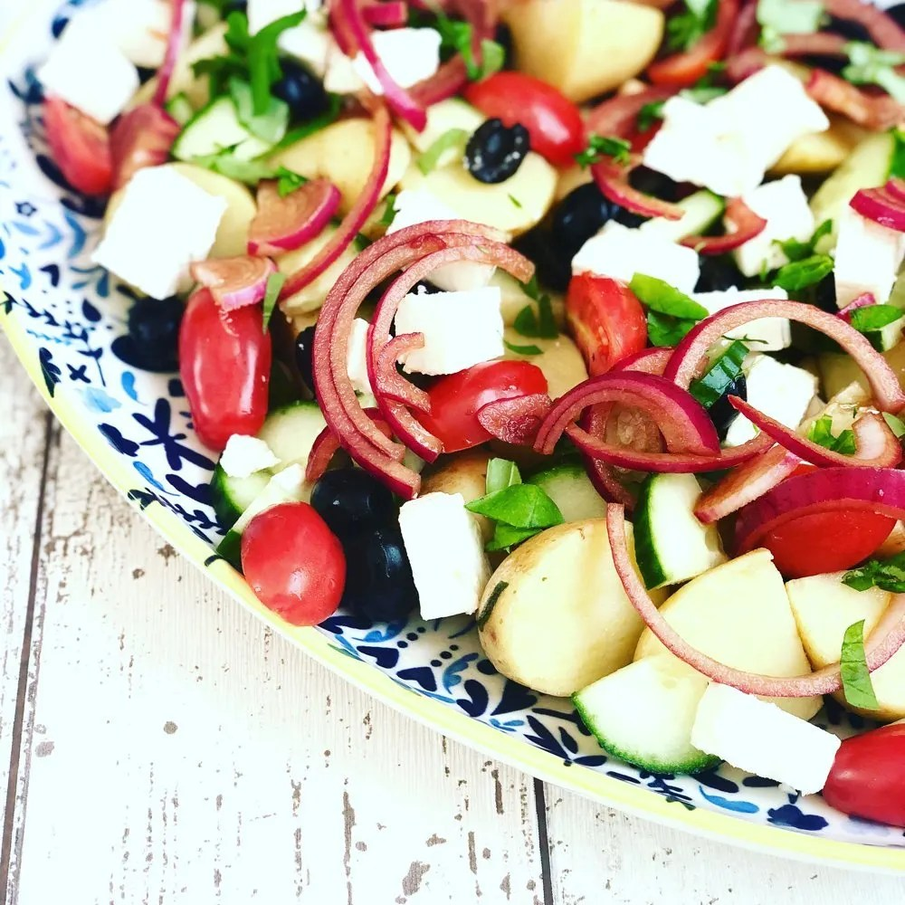 platter of Greek potato salad with feta cheese and herbs.