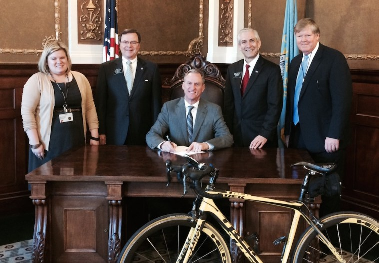 Governor Dennis Daugaard (center) signs HB 1030 into law, March 11, 2015. Attending the signing ceremony are (L to R) Megan Myers, government relations director, American Heart Association; Sen. Mike Vehle (R-20/Mitchell); Rep. Fred Deutsch (R-4/Florence); and Dean Krogman, lobbyist.