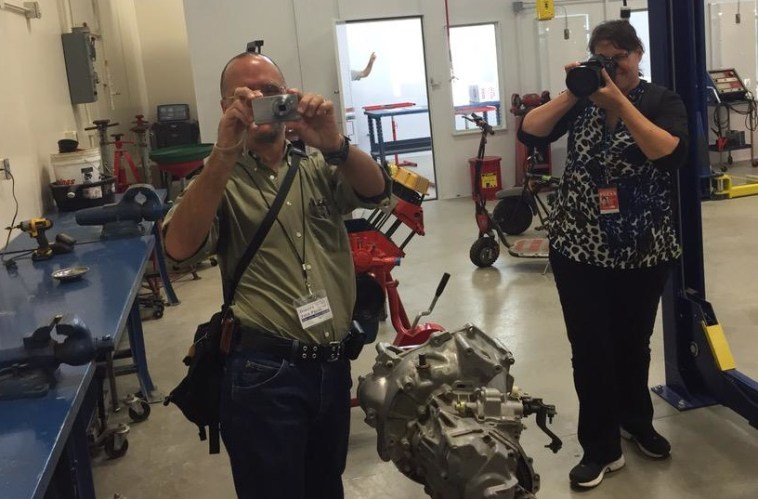 Dakota Free Press blogger C.A. Heidelberger and Aberdeen American News reporter Katherine Grandstrand, A-TEC Academy auto shop, Aberdeen, South Dakota. Photo by Tony Venhuizen, SD Governor's office, 2015.09.01.