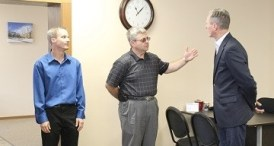 Walter Schoenfish (center) gives Governor Dennis Daugaard (right) a tour of Schoenfish & Co., Inc.'s Parkston office, while Rep. Kyle Schoenfish (left) looks on adoringly. Photo from City of Parkston, 2014.08.27.