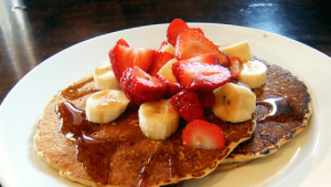 Pancakes toped with strawberries and banana slices