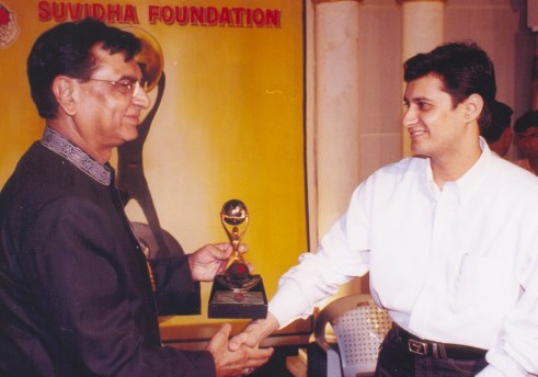 Dale Bhagwagar prepares to receive the Suvidha Gaurav Achiever Award from Shankar Lalwani, chairman of Suvidha Gaurav Foundation.