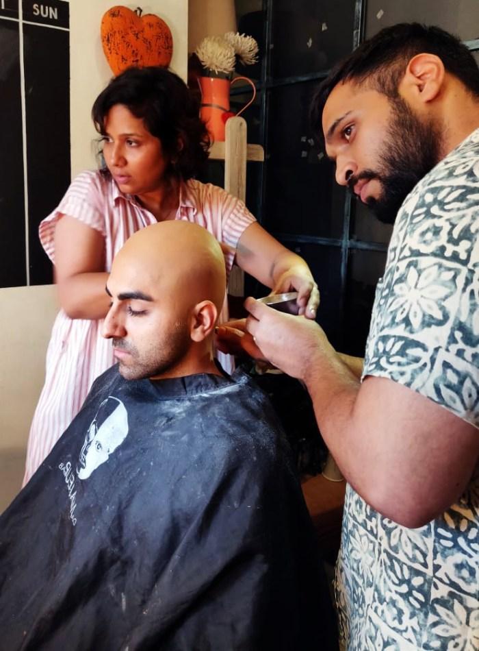 Preetisheel Singh working on Ayushmann Khurrana's look on the sets of Bala. Pic 3.