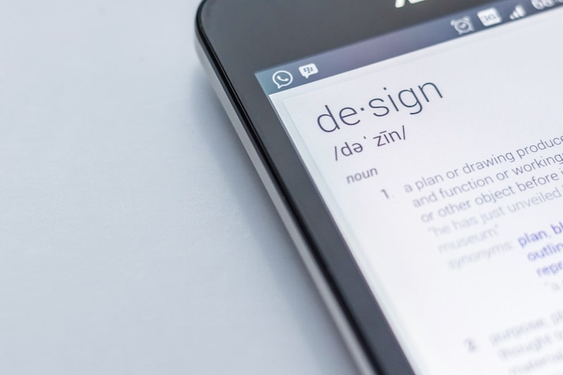 """photo of smartphone with definition of """"design"""" on its screen"""