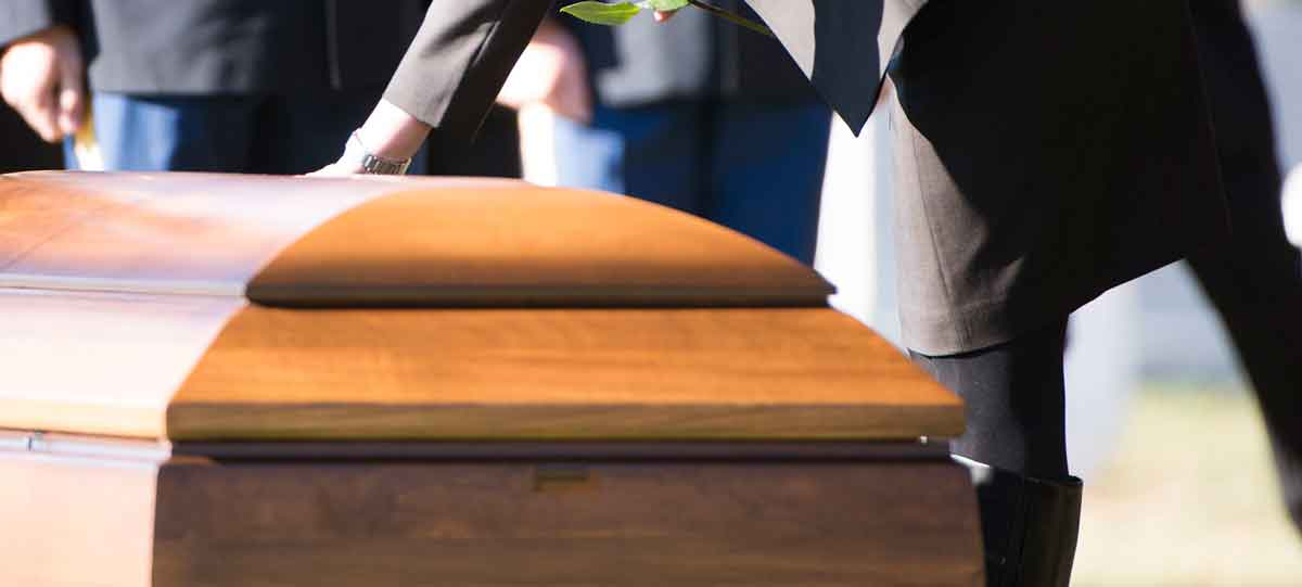 Funeral service woman touching casket, Dallas Wrongful Death Lawyer