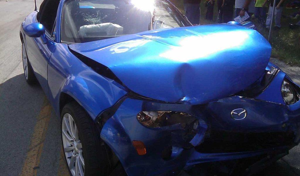 Damaged blue car for claim lawyer in Dallas