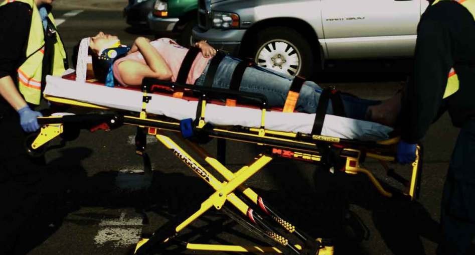 Woman on backboard at accident scene. Dallas Soft Tissue Injury Lawyer