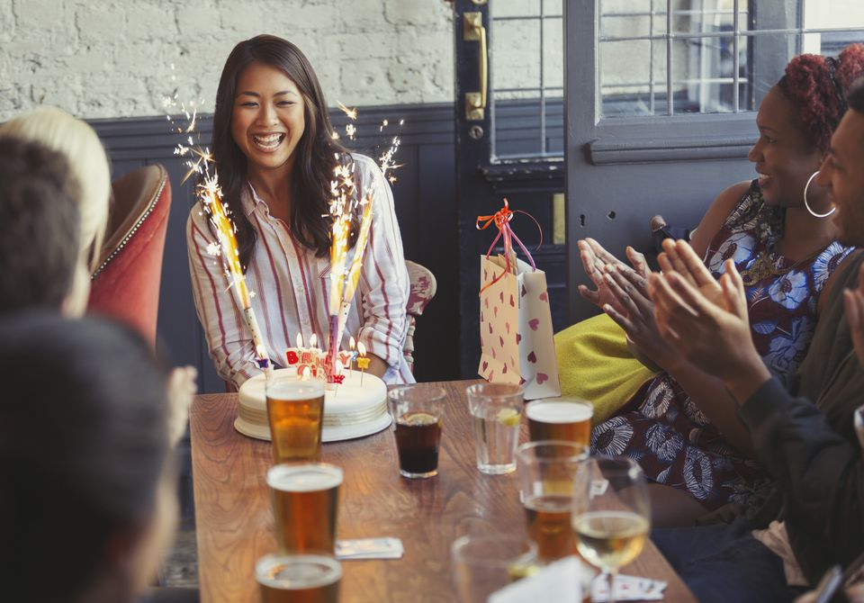 friends-clapping-for-happy-woman-with-fireworks-birthday-cake-at-restaurant-table-702545435-5a99ae54ff1b78003612082f