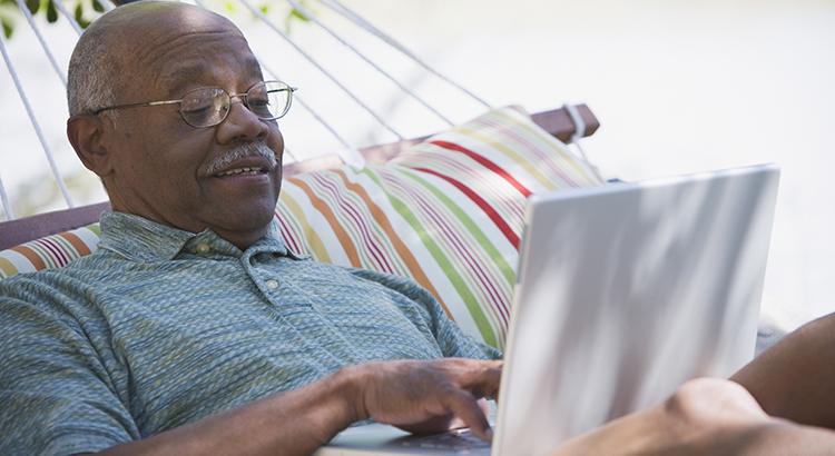 Senior African man using laptop in hammock