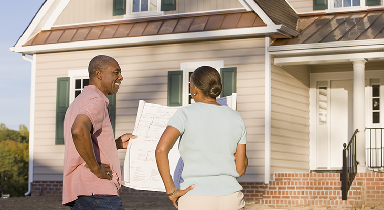 African couple holding blueprint in front of house
