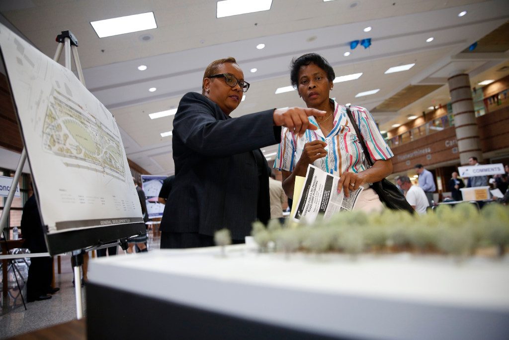 Sandra Williams (left), environmental specialist with TxDOT, speaks to Linda Smith, an Oak Cliff resident, before a public hearing on the proposed Oak Cliff Deck Park at Yvonne A. Ewell Townview Magnet Center in Dallas on April 25. The deck park, similar to Klyde Warren Park, would be over Interstate 35E in Oak Cliff.(Rose Baca/Staff Photographer)
