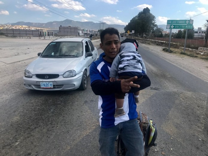 Jonathan David Cardenas, 32, and his 8-month-old son, Julio Cesar, along a main thoroughfaire in Guanajuato, Mexico, the week of January 22, 2019. They were asking for handouts from motorists and were part of a caravan that originated in San Pedro Sula, Honduras, headed for Houston.(Alfredo Corchado/Staff Photo)