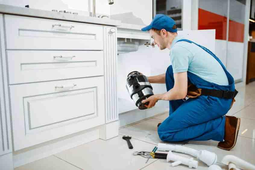 Male plumber in uniform installing disposer