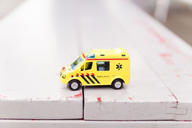 A toy ambulance on top of a white wooden bench