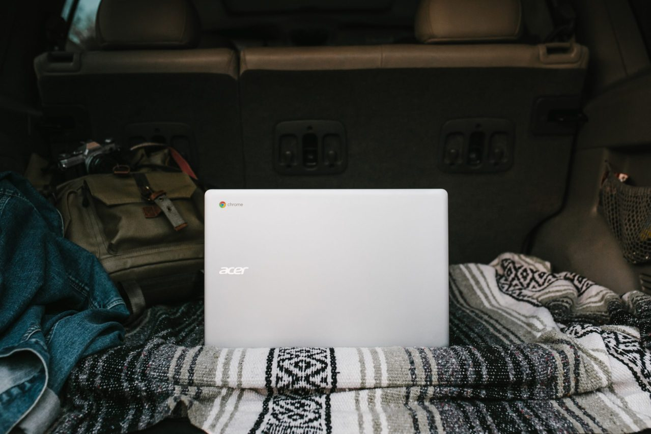 Grey laptop on top of a patterned blanket in a dark room.
