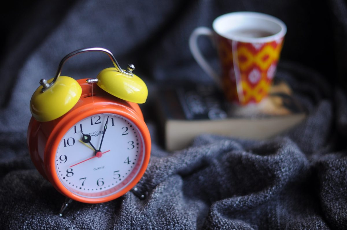 Alarm clock in bed with tea and book