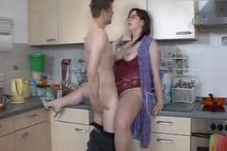 Zralá matka podrží mladému malířovi v kuchyni