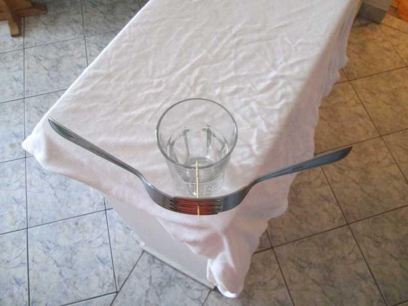 2 furculițe și o scobitoare pe marginea unui pahar