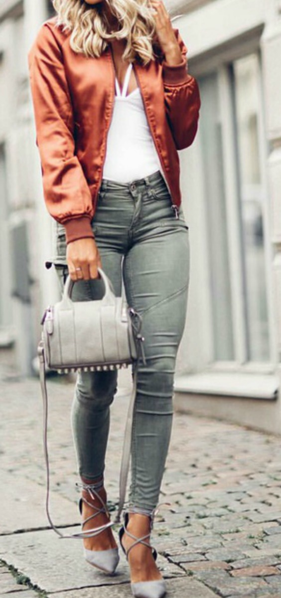 A women on the street wearing a satin bomber jacket with jeans and a white top and ballet flats