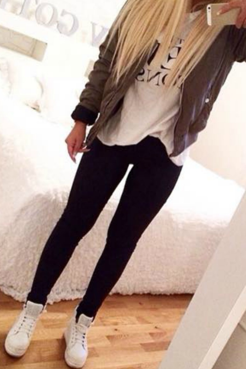 a blond teen girl wearing a fall winter outfit black jeans white sneaker a t shirt and a green bomber jacket