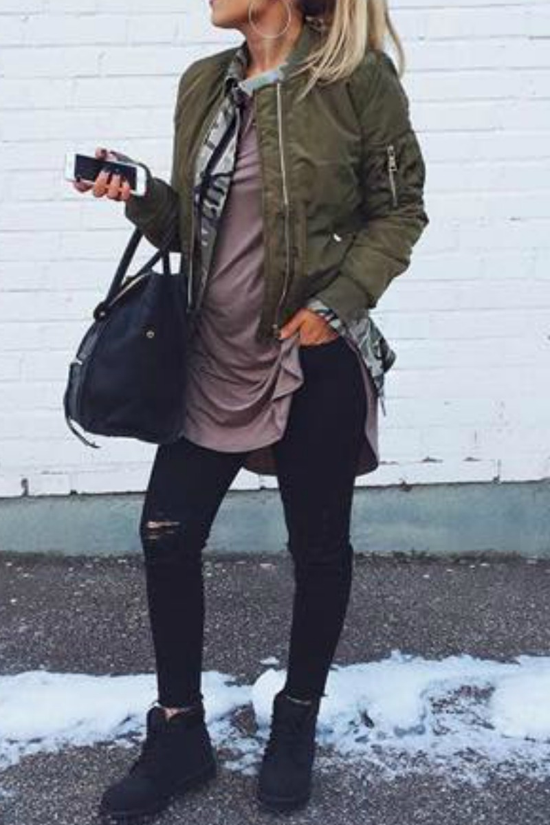 a women wearing wearing a fall outfit with a green bomber jacket and black jeans and black timberland boots