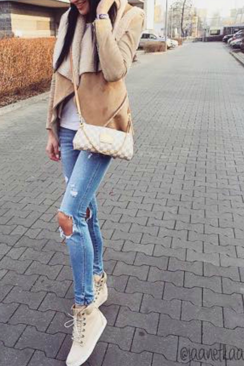 A teen girl wearing a Winter Outfit Idea with Light Blue Jeans on the street