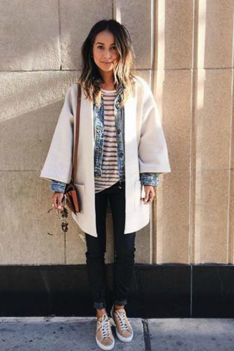 a women in a street style outfit for fall or winter dark blue jeans sneakers and a denim jacket with a wool cream coat over it