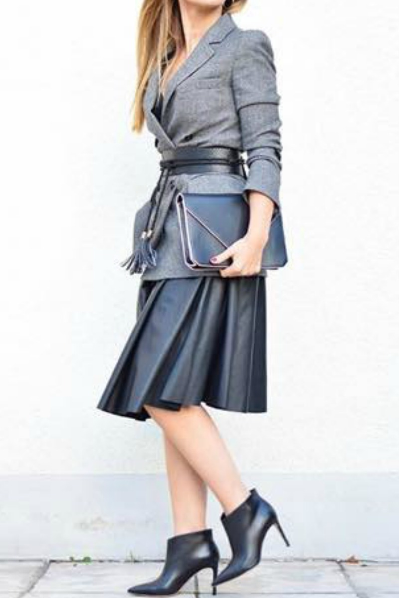 a women wearing a long pleated skirt ankle boots and a grey blazer with waist belt