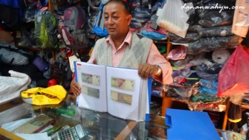 pemilik toko perlengkapan outdoor - menunjukan koleksi uang rupiah