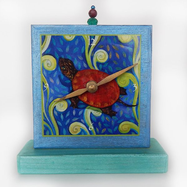 Turtle Precious Time Shelf Clock is hand painted shimmery blue and aqua on a wooden base, an archival print of the Red Turtle is the clock face.