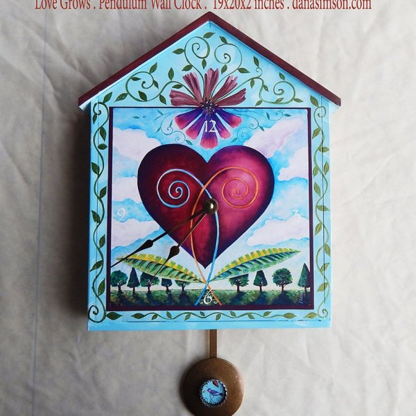 Love Grows Wall Clock is hand painted light blue with vines all over. the main heart growing in a garden image is a print on the house-shaped wooden clock. It has a pendulum.