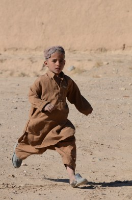 A little boy running to greet us in Shah Joy