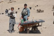 A young Afghan boy selling snacks at teh Stockyard while one of our AFghan National Police (ANP) escorts looks on